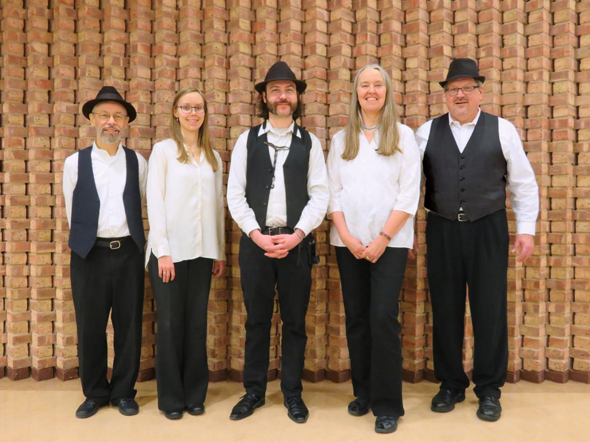 Ensemble M'chaiya as a quintet standing along a brick wall.